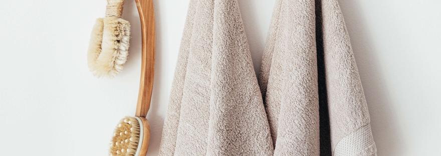 """alt= """"Brosse de douche et des serviettes de bain suspendues"""""""